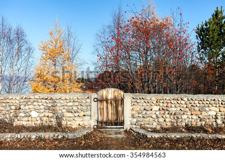 Seasons. The stone fence with a gate in the open air overlooking the sea. masonry. Blue sky. Lake View. Exit.  trees. Green grass. Yellow leaves. Horizon. Horizontal - stock photo