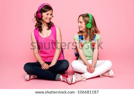 Seated beautiful teenagers looking at each other. Pretty schoolgirls - stock photo