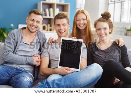Seated friends hold up computer tablet and smile as sunlight streams through nearby windows in blue colored living room - stock photo