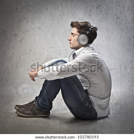 Seated young man listening to music - stock photo