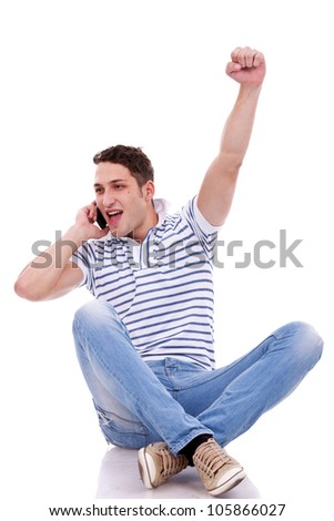 seated young man talking on the phone and winning something - stock photo