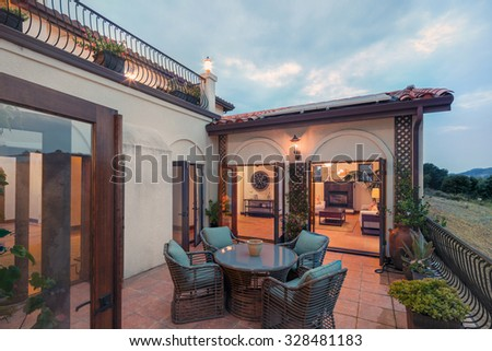 Seating arrangement, in Spanish style home night with open doors leading into home with  open floor plan and terrace. - stock photo