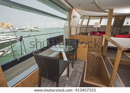 Seating in the salon area of a large luxury motor yacht with big panorama window showing view over tropical ocean marina - stock photo
