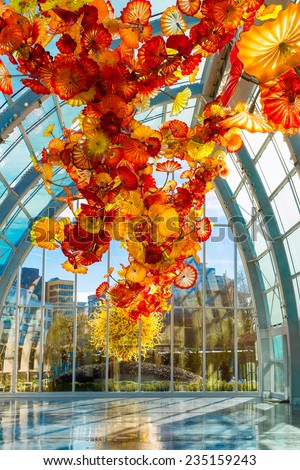 SEATTLE-DEC 1, 2014: Chihuly Garden and Glass museum featuring one of Dale Chihuly's largest sculptures suspended from the ceiling of the glasshouse. City buildings are seen in the background. - stock photo