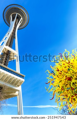 SEATTLE-DEC 1,2014:Unique perspective of two Seattle icons, the Space Needle and the Chihuly Garden and Glass Museum next door, with a glass sculpture seen in the foreground. Blue sky with copy space. - stock photo