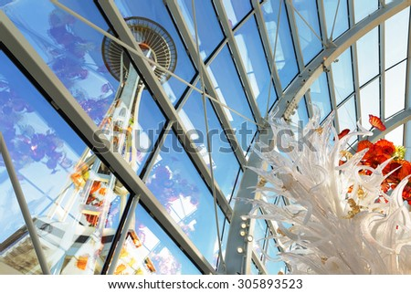 SEATTLE-DEC 1,2014: View of the Space Needle from inside the Chihuly Garden and Glass museum conservatory next door. Unique perspective. Reflections. Focus is on the glass sculpture in the foreground. - stock photo