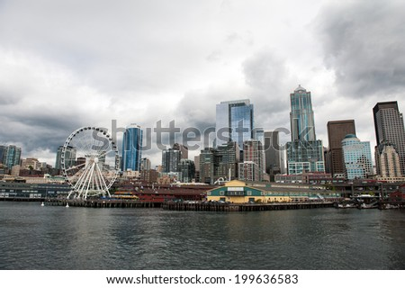 SEATTLE - MAY 10: A view of the Seattle Great Wheel, Pier 57, and Seattle skyline seen from Elliott Bay on May 10, 2014. - stock photo