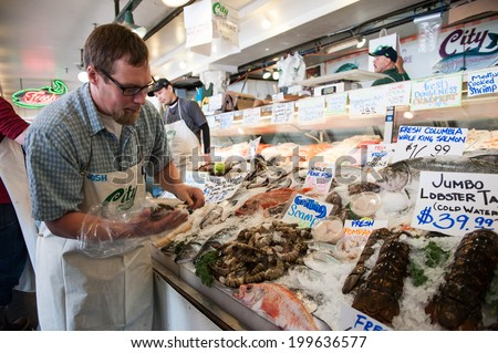 SEATTLE - MAY 10: An employee of City Fish Co. arranges shrimp at Pike Place Market in Seattle on May 10, 2014. Opened in 1917, City FIsh Co. is one of the longest-running fish markets. - stock photo