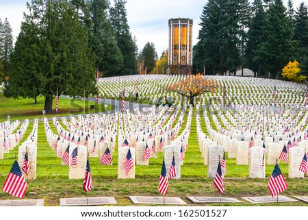 "SEATTLE - NOV 11: Flags at Headstones in Veterans Memorial  Cemetery at Evergreen Washelli Memorial Park, the ""Arlington of  the West,""  in Seattle WA on November 11, 2013. Chimes Tower in background. - stock photo"