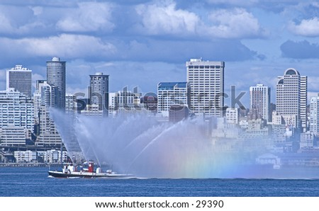 Seattle's fireboat sprays water, creating a rainbow - stock photo