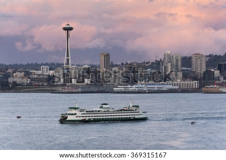 Seattle Skyline. A ferryboat crosses Elliott Bay in front of the Seattle skyline and the historic Space Needle which is a leftover from the 1962 World's Fair during a lovely sunset. - stock photo