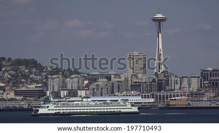 SEATTLE, U.S.A. - JUNE 01, 2014: A Washington State Ferry crosses in front of the Space Needle in Elliot Bay.  Washington State Ferries operates the largest ferry system in the United States. - stock photo