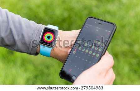 SEATTLE, USA - May 19, 2015: Man Comparing Activity App on Apple Watch and iPhone6 After Working out. Multiple Day View. - stock photo