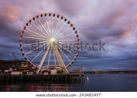 SEATTLE, USA - OCTOBER 14, 2014:  The Big Wheel stands against a cloudy sunset at the end of a pier on Elliott Bay at night in Seattle, Washington on October 14, 2014. - stock photo