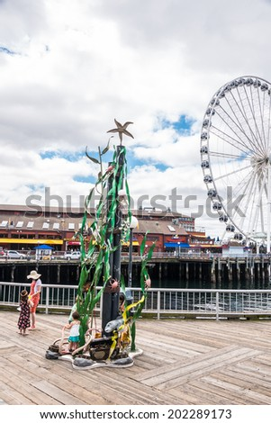 SEATTLE, WA - JUN 24, 2014: Whimsea Statue in Waterfront Park with Pier 57's Miners Landing shopping, restaurant, and entertainment complex and the Great Ferris Wheel in the background, Seattle, WA. - stock photo