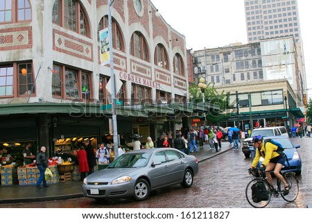 SEATTLE, WA - JUNE 9: Merchants and tourists at the famous Pike Place Market on June 9, 2007. This public market opened in 1907 and continues to be one of the oldest public farmers' market in the USA. - stock photo