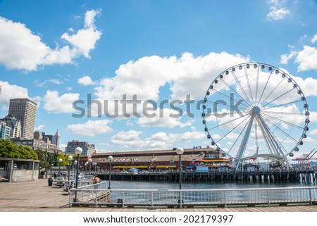 SEATTLE, WA - JUNE 24, 2014: Pier 57 with its Great Ferris Wheel and Miners Landing, a popular tourist destination on Seattle, Washington's waterfront. - stock photo
