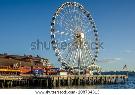Seattle, WA, USA - July 6, 2014: People waiting to ride the Great Wheel at Sunset. Since the opening, in June 2012, it has become an icon of the city and a destination for tourists and locals alike. - stock photo