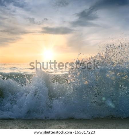 Seaview postcard. Beautiful sunset at the sea with shorebreak splashes on sandy beach - stock photo
