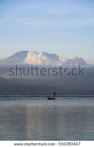 seaweed farmer on his small boat of the coast of nusa lembongan island opposite the gunung agung volcano bali indonesia - stock photo