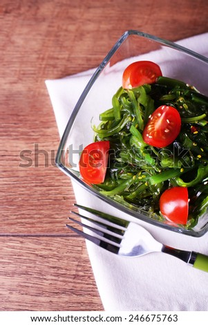 Seaweed salad with slices of cherry tomato in glass bowl on napkin and wooden table background - stock photo