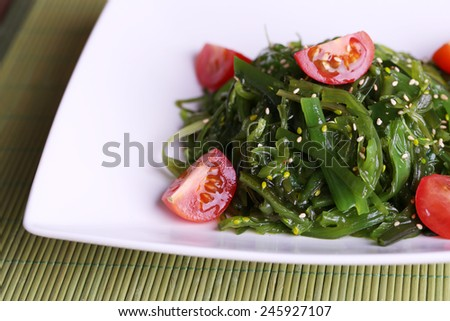 Seaweed salad with slices of cherry tomato on bamboo mat background - stock photo