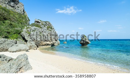Secluded tropical beach cove, coral rocks and clear blue water, Okinawa, Japan - stock photo