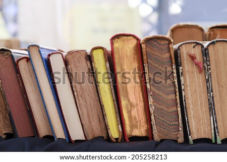 Second hand books leaning against each other for sale in a street book market - stock photo
