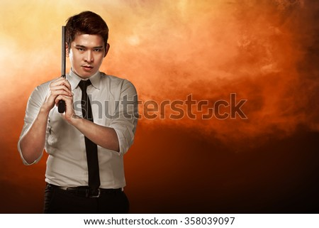 Secret agent holding gun ready to fire - stock photo