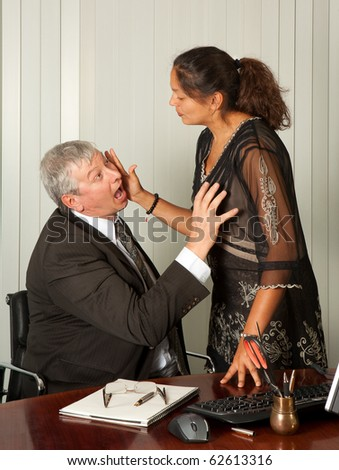 Secretary defending herself with her scissors against intimacy by her boss - stock photo