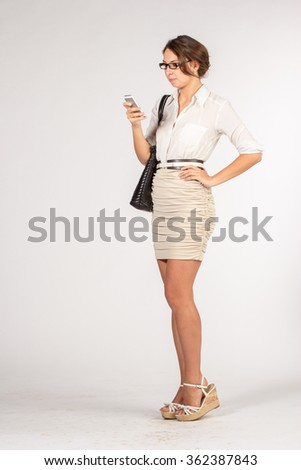 Secretary girl in a short beige skirt with sunglasses, bag and mobile phone - stock photo