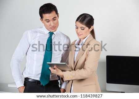 Secretary planning dates for her boss with a tablet pc in the office - stock photo