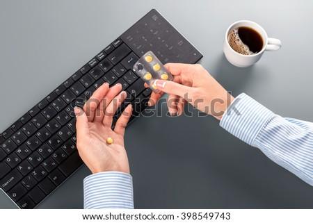 Secretary's hand taking yellow pill. Secretary taking pills at workplace. Lady undergoes huge stress. Clerk's blood pressure is rising. - stock photo