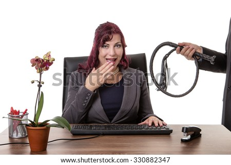 secretary sitting at desk with a man standing to the side holding a whip - stock photo