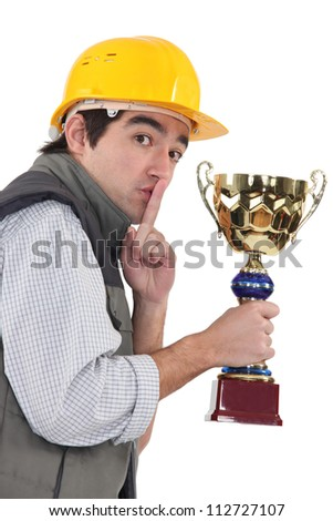 Secretive construction worker with a trophy - stock photo