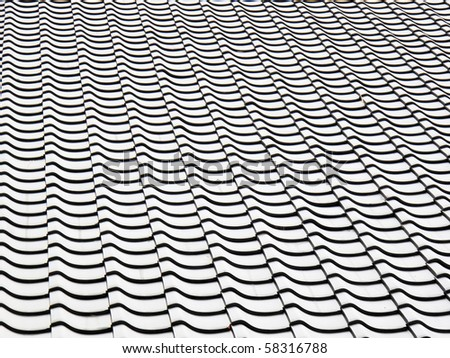 Section of a black and white tile roof - stock photo