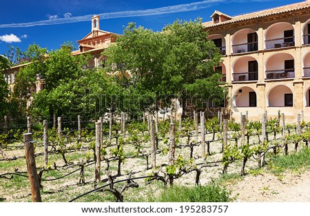 Secular building surrounded by agricultural plantations. An old Catholic monastery. - stock photo
