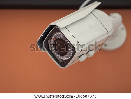 Security Camera,CCTV with orange wall background. - stock photo
