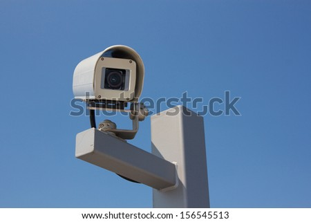 Security camera facing right before the background of a clear blue sky. - stock photo