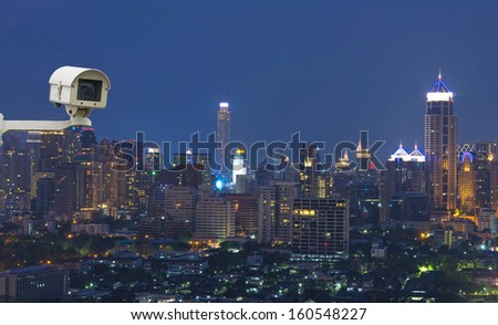 Security camera monitoring the traffic movement on top view of cityscape. Skyscraper rooftop. - stock photo