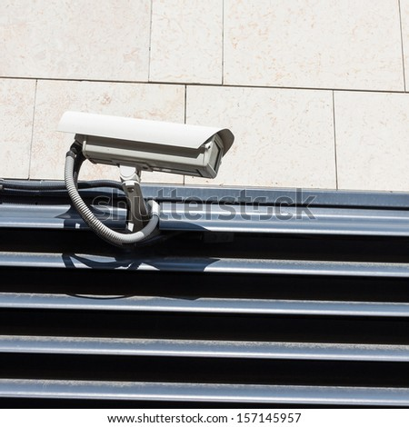 Security camera on the wall - stock photo