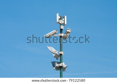 security cameras and floodlights mounted high on a pole to oversee an industrial area - stock photo