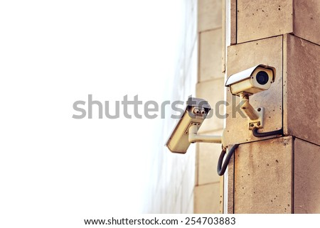 Security CCTV camera mounted on the building wall as apart of private property protection system or Big Brother Concept with white copy space - stock photo