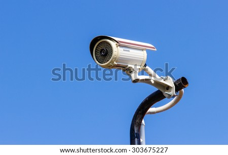 Security CCTV camera on blue sky background. - stock photo