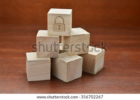Security concept - Stacked up cube with padlock on the top on wooden background. Image slightly defocussed with dramatic lighting and warm image temperature. - stock photo