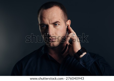 Security detail, bodyguard holding earpiece. Studio shot. - stock photo