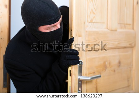 Security - disguised burglar breaking in an apartment or office to steal something - stock photo