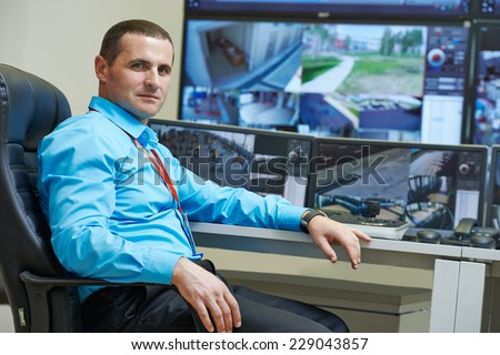 security executive chief in front of video monitoring surveillance security system - stock photo