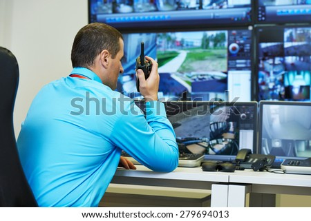 security guard watching video monitoring surveillance security system - stock photo