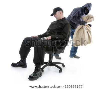Security man sleeping on armchair being unaware of masked burglar stealing behind his back - stock photo